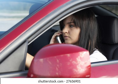 a cute teen driving on cell phone