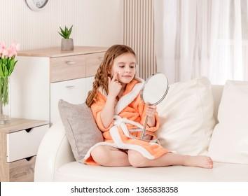 Cute teen girl applying skin-care cream on her face