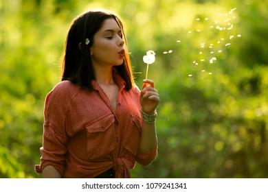 Cute teen girl blowing dandelion in spring season. Trendy summer girl blowing seeds allergy season