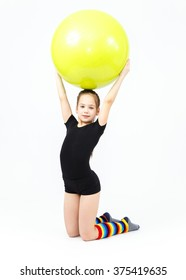 Cute teen girl doing gymnastics exercises with fitness ball