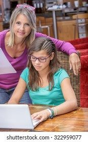 cute teen girl doing its homework in complicity with her mother