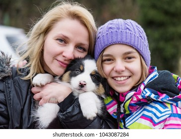 Cute teen girl and her mother playing and hugging with their new puppy Australian Shepherd dog, outdoors. Friendship and care concept.