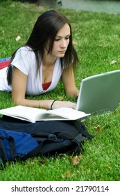 Cute teen girl laying down on the grass studying with her laptop
