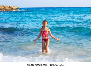 Cute Teen Girl playing In Sea Waves. Jump Accompanied By Water Splashes. Summer  Day, Happy childhood, Ocean Coast concept