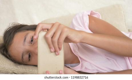 Cute teen girl sleeping on sofa with phone in hand. Lack of sleep. close-up,