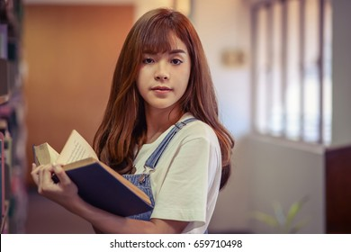 Cute Teen Girl Stand Reading Book In The Library Close Up
