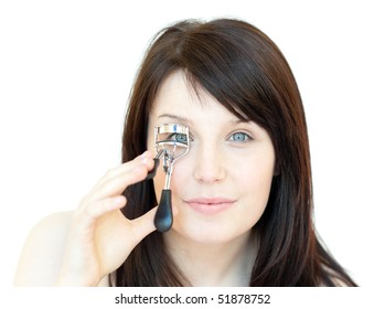 Cute teen girl using an eyelash curler against a white background