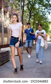 Cute teen girl walking down the street to school