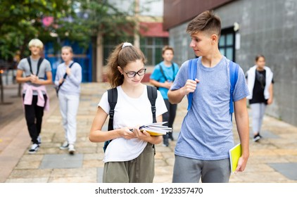 Cute teen girl walking with her classmate outside college building on autumn day, going to lessons.