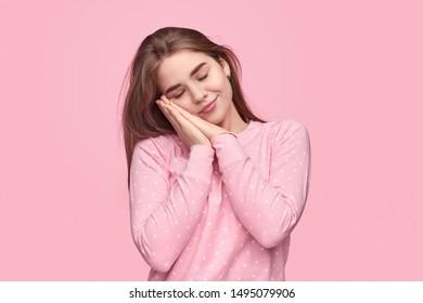 Cute teen girl in warm sleepwear keeping hands under cheek and sleeping against pink background