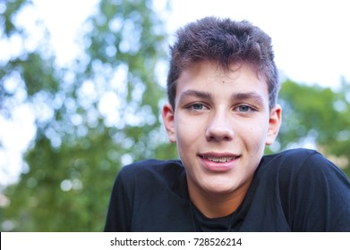A cute teen rests after outdoor exercise. He has a cheerful face and braces on his teeth