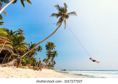 Cute teenage boy having fun swinging on a rope at tropical island beach in Sri Lanka