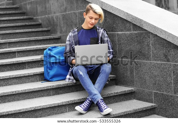 Cute teenage boy with laptop sitting on stairs outdoors