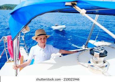 Cute teenage boy sailing on a luxury catamaran boat