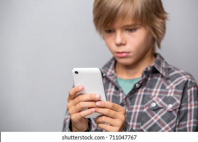 Cute teenage boy using cellphone isolated over grey background, focus on phone