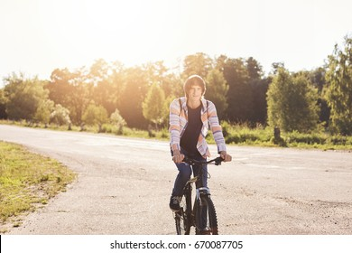 Cute teenage boy wearing shirt carrying backpack riding his bicycle having rest during his ride in suburb of city. Young schoolboy with trendy hairstyle resting outdoors with his modern bike