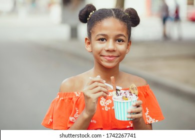 Cute teenage girl eating ice-cream in the street