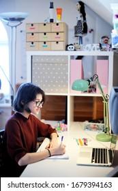 Jolie adolescente en lunettes pendant son éducation à distance