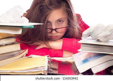 Cute teenage girl with glasses, surrounded by books and school work, looking frustrated