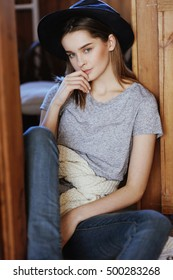 Cute teenage girl in a hat in country style resting in wooden house in the village