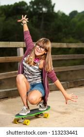 Cute teenage girl practicing on skateboard outdoors.
