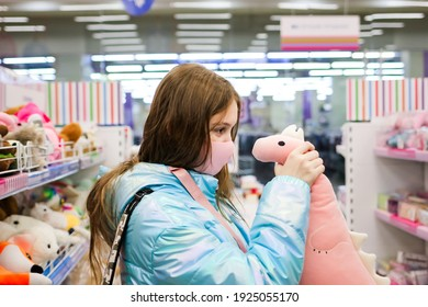 A cute teenage girl in protective medical mask choosing toys or gifts in the store.