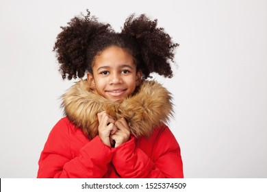 Cute teenage girl in red winter parka against white background