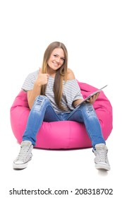 Cute teenage girl with tablet gesturing thumbs up. Beautiful young blonde student girl sitting on pink beanbag holding digital tablet smiling wearing casual clothes isolated on white background.