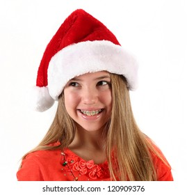 Cute teenage girl wearing Santa hat for Christmas on white background
