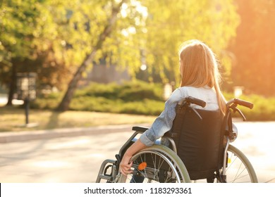 Cute teenage girl in wheelchair outdoors