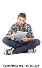 Cute teenage guy using tablet computer smiling