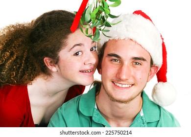 Cute teenage Latina girl ready to kiss her boyfriend under the mistletoe.  White background.  Christmas theme.
