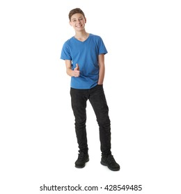 Cute teenager boy in blue T-shirt standing and pointing forward over white isolated background full body