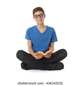 Cute teenager boy with book in blue T-shirt, glasses and lotus posture over white isolated background