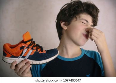 cute teenager boy kid funny grimacing with stinking trainer shoe close up photo