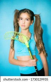Cute teenager girl with long blond hair in a sports uniform with a floorball club in hands on a blue background in the studio. Sports fashion. Sport for youth.