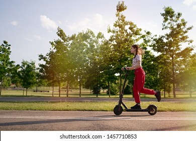 Cute teenager girl riding electric kick scooter in the park at sunset