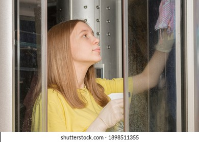 cute teenager girl washes the shower stall with gloves. She holds detergent and a rag in her hands, wipes the glass walls of the shower stall. Horizontal photo.