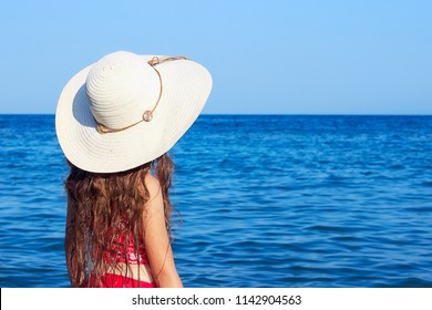 Cute teenager girl wearing at a big hat and swimwear looking at the sea. Place for text