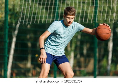 Cute Teenager in green t-shirt with orange basketball ball plays basketball on street playground in summer. Hobby, active lifestyle, sports activity for kids.