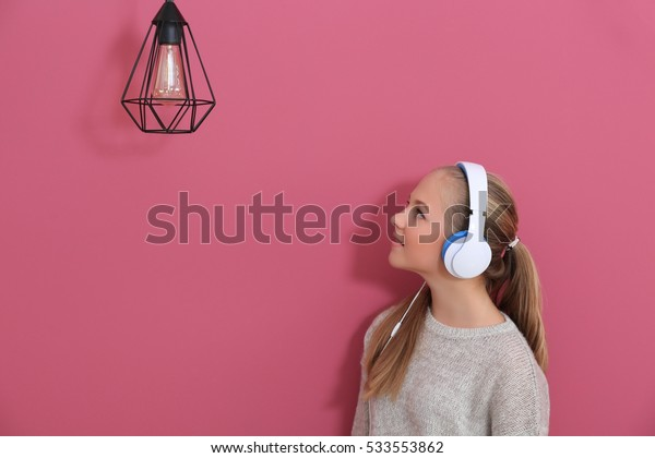 Cute teenager with headphones on wall background