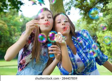 Cute teenager playing with soap bubbles in summer