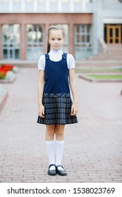 Cute teenager schoolgirl in uniform with ponytails in a plaid skirt, posing for the camera.