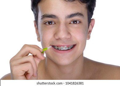 Cute teenager with white background, wearing braces on his teeth. Use a small toothbrush.