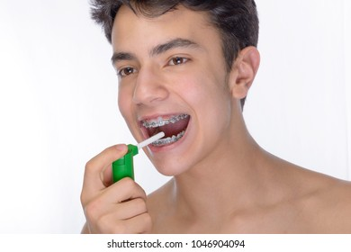 Cute teenager with white background, wearing braces on his teeth. Spray a disinfectant mouthwash in the throat.