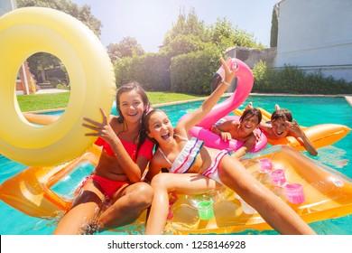 Kleine Tees spielen mit Schwimmschwimmen im Pool