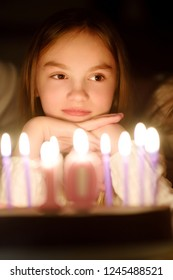 Cute ten year old girl making a wish before blowing candles on her birthday cake. Child celebrating her birhday. Birthday traditions.