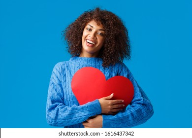 Cute and tender funny, smiling african-american female with afro haircut, press big red heart sign to chest and embrace it with delighted charming grin, showing love and affection, blue background
