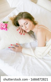 Cute tender young girl with blond hair in white clothes and lace underwear surrounded by pink peonies on the bed on the bed in the studio. Spring and flowers. Beauty and Fashion