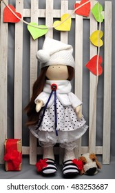 cute textile doll in a white dress with brown hair